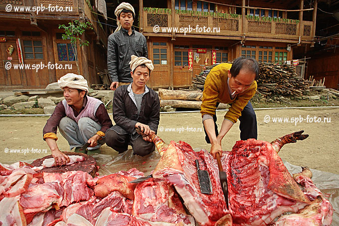 Разделка свиной туши на дороге в деревне Зенчон.  Белые повязки на головах мужчин, символизируют скорбь.