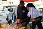 На фото, девушка мусульманка, с острова Занзибар, покупает свежевыжатый тростниковый сок