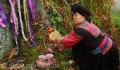 На фото: Женщина племени Яо совершает поминальный ритуал на могиле своего родственника