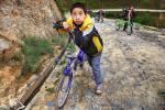 Подростки катят велосипеды в горку по дороге из Zhaoxing в Jilun