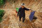 Китаянка, представительница малой народности Dong, идет по дороге, соединяющей деревни Жаосин и Jilun