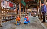 Два младенца устроили гонки на детских мотоциклах по мосту Ветра и Дождя, в деревне Чжаосин, Гуйчжоу, Китай