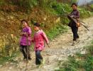 Жительница деревни Зенчон несет домой дрова для очага, ее сопровождают две девочки в ярких нарядах, изготовленных в этой же деревне