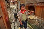 Мужчина народности Dong с парой грязных, пустых ведер, висящих на приспособлении типа коромысла, идет по узкой деревенской улице