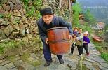 Старик китаец, с изуродованным лицом, тащит бочку вверх по дороге в горной деревне