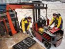 Грузовик с манипулятором Palfinger, и рабочие, извлекающие мотор из автопогрузчика, фотография