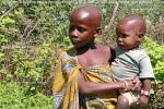 Пластмассовый браслет на руке масайского ребенка и футболка на его теле, признак того, что племя живет среди современной цивилизации
