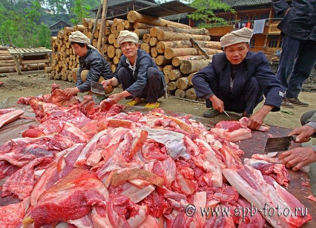 На фото: Жители деревни Zengchong разделывают свиней на улице